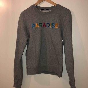 Grå sweatshirt från gina med texten paradise broderat i REGNBÅGENS FÄRGER! Väldigt sparsamt använd! Frakten ingår i priset!!