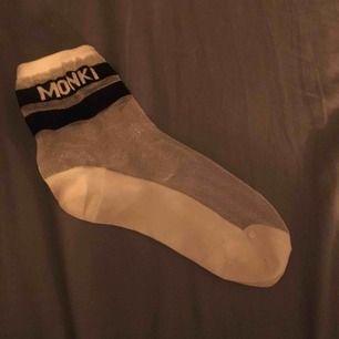 """Sheer socks från Monki. Strumporna är i ankellängd, glittriga och har texten """"Monki"""" upp mot benet (se bilder). Materialet är bekvämt och strumporna har aldrig används och är i mycket gott skick. Hör av dig vid ev. frågor!!"""