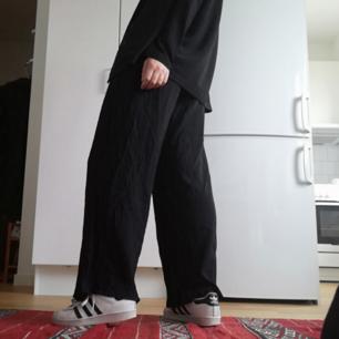 Svarta diskret kritstrecksrandiga vida byxor med hög midja från Zara i stl XS. Gjorda i ullblandning. Lite slitna längst ner på byxan annars bra skick! Frakt 59 kr.