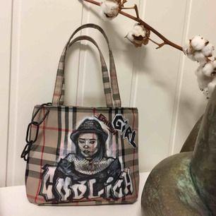 En liten väska i fint skick! Handmålad av mig, lite alternativ stil med Burberry mönstret som bakgrund runt hela väskan. Hänger en kedja runt ena sidan i bra kvalité! Frakten är inräknad i priset!