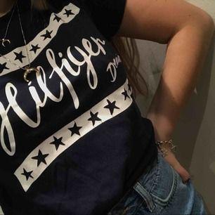 Snygg T-shirt ifrån Tommy Hilfigher! Är i storlek M men passar mig som är XS-S om man stoppar in den lite! Fraktkostnad tillkommer