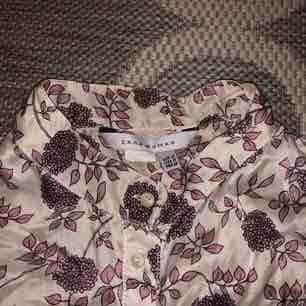 """Blommig retro blus från Zara Woman köpt second hand. Står M på lappen men passar mig som har XS/S. Materialet är av siden och ärmarna är """"puffiga"""". Inga defekter, jättefint skick"""