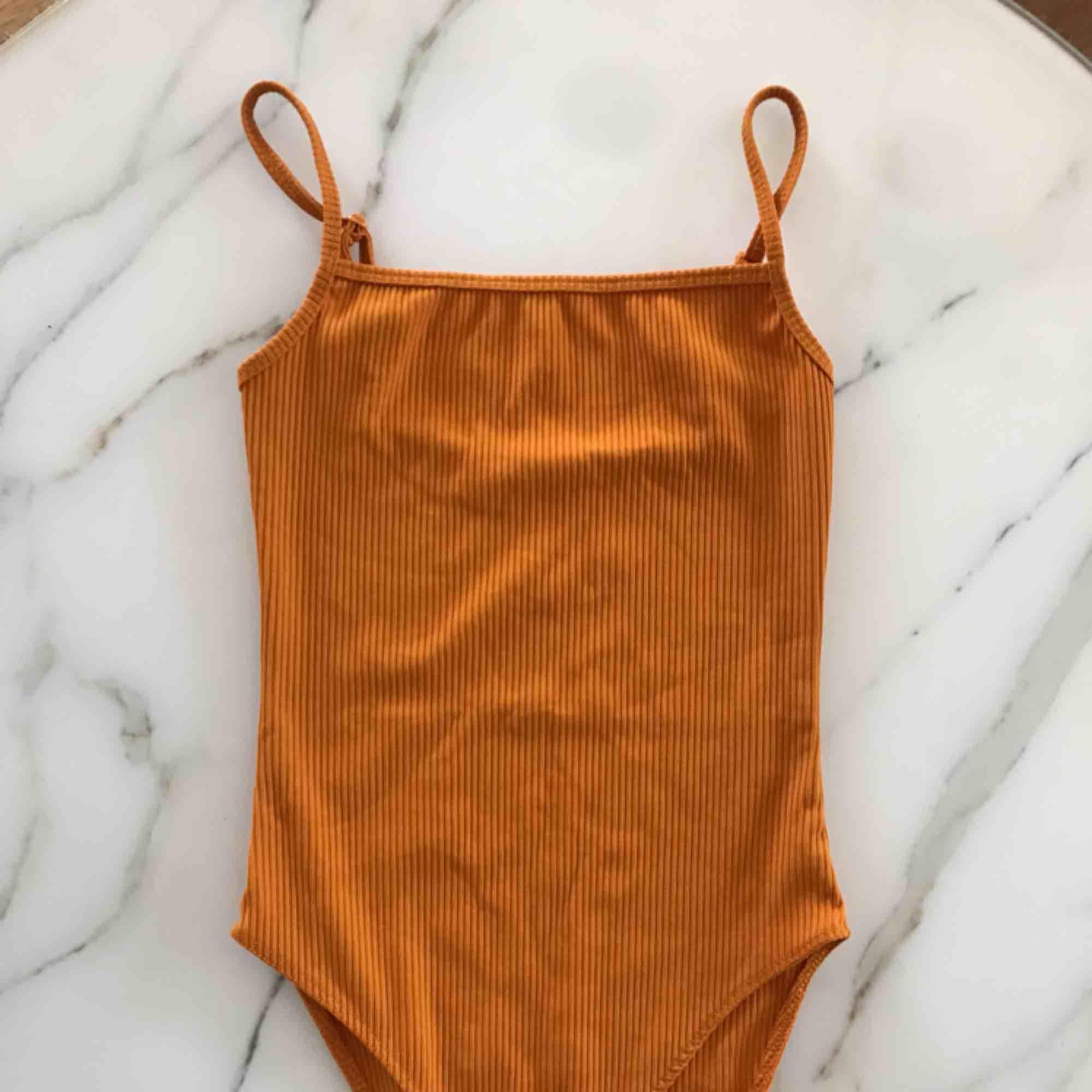 Orange ribbad body från Gina Tricot, inköpt förra sommaren. Suuuperfin och riktigt snygg när man är brun. Fraktar men köparen står för fraktkostnad!. Toppar.