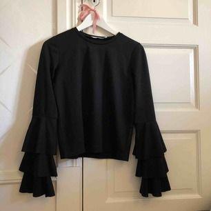 Svart tröja/blus från NA-KD med volanger. Sparsamt använd.