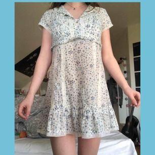 Sötaste klänningen ifrån Ellos med små blåa blommor. Kragen kan vikas på två olika sätt (se bild 3). Står att det är en 40 men den sitter perfekt på mig som är en S/XS. Den är hyfsat kort och slutar mitt på låret på mig som är 166! Frakt: 25kr