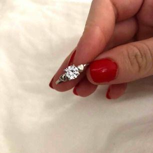 En as fin ring från Gina med en stor silvrig diamant i mitten och två små silvriga hjärtan vid sidorna!   Kontakta mig vid intresse eller frågor!