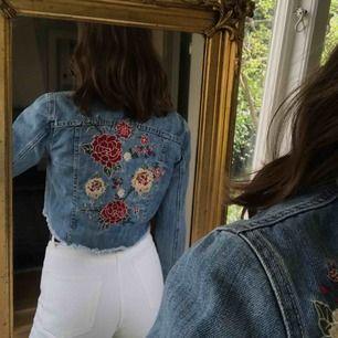 Jeansjacka i midjekort modell med broderade rosor på ryggen samt på framsidan ovanför båda fickorna! Är i nyskick!