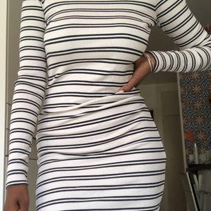 Vit klänning med svarta ränder. Ribbad i tyget. Går att   Välja om man vill ha den lite längre eller kortare.