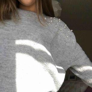 En grå stickad tröja med pärlor på axen. Den är väldigt stor i storleken. Inte använd så många gånger.  Köpare står för frakt.