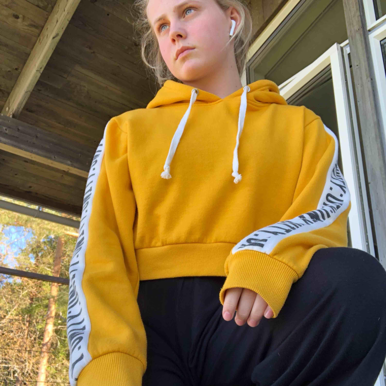 Senaps-gul croppad hoodie men svart-vit text på ärmarna . Huvtröjor & Träningströjor.