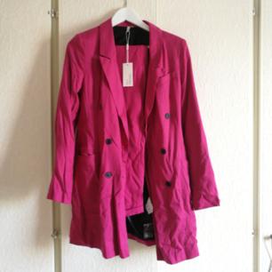 Two-piece kostymset från nelly i fuchsia rosa färg! Skiit snygg endast använd 1 gång, behöver stryckas! Kavajen är i storlek 36 och byxorna i storlek 38