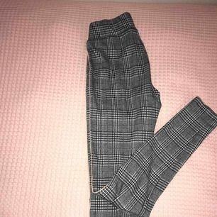Ett par svarta & vita kostymbyxor i tightsmaterial med en rosa rand på sidan på båda sidorna! Använda, men är i bra skick! Mycket bekväma 🥰