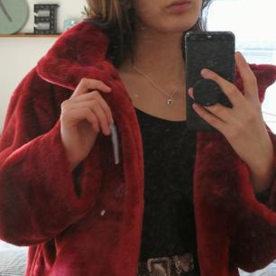 Trendig röd jacka i kort fakepäls, strlk XS men lite oversized. Hög krage och kan stängas med knappar. Fick med den från en inspelning och har aldrig använt den. Tror att nypris är 400 kr🌸
