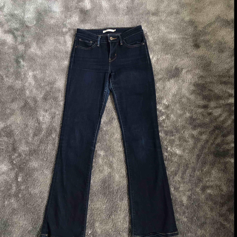 Jättefina mörkblå bootcut jeans från Levis. Storlek 25 i midjan och benen är avklippta och uppsydda att passa för någon som är ca 155-160. Ett litet märke på baksidan av ena benet däravpriset. Annars är dem i bra skick. Skriv för fler bilder. . Jeans & Byxor.
