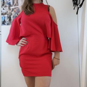 Jättefin klänning i stark röd färg. Öppna axlar och öppen rygg. Även öppen vid midjan (se sista bild) Tajt kjol som ger fin figur och vida ärmar. Aldrig använd!