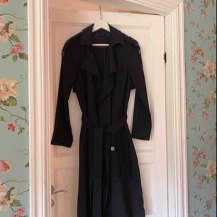 Jättefin Trench Coat från Gina Tricot, köpt för ca 500kr. Knappt använd och i jättefint skick. Passar mig som är S men blir lite kort i armarna. Snörning runt midjan men kan tas bort.