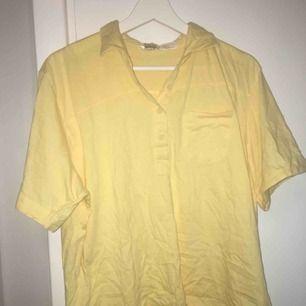 En ljusgul piké från en second hand affär. Från Lindex. Tröjan har en ficka på bröstet. L passar även en XS/S om man vill ha den oversize, som jag hade.