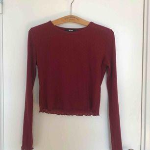 Vinröd tröja fin bikbok med fina detaljer på ärmarna och nedre kanten