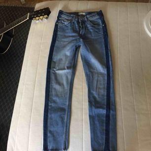 Blå jeans med mörkare sträck längst sidorna från Gina Tricot. Modellen är tajt, lite vidare ner mot vaderna samt avklippta sömmar längst ned. Knäppning med knappar. Köparen står för frakten, swish ☺️