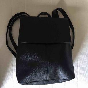 Svart skinn-imiterad ryggsäck från Primark, köpt i England. Aldrig använd, mycket bra skick. Justerbara axelremmar, gulfärgade detaljer. Endast ett fack. Köparen står för frakt. Via Swish ✌🏼