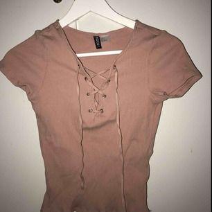 T-shirt i en fin gammelrosa/nude färg med snörning. Använd fåtal gånger. Sitter otroligt snyggt på och formar fint🌼 mer bilder kan fås vid intresse, kan fraktas
