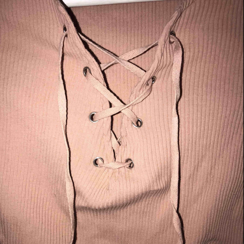 T-shirt i en fin gammelrosa/nude färg med snörning. Använd fåtal gånger. Sitter otroligt snyggt på och formar fint🌼 mer bilder kan fås vid intresse, kan fraktas. T-shirts.