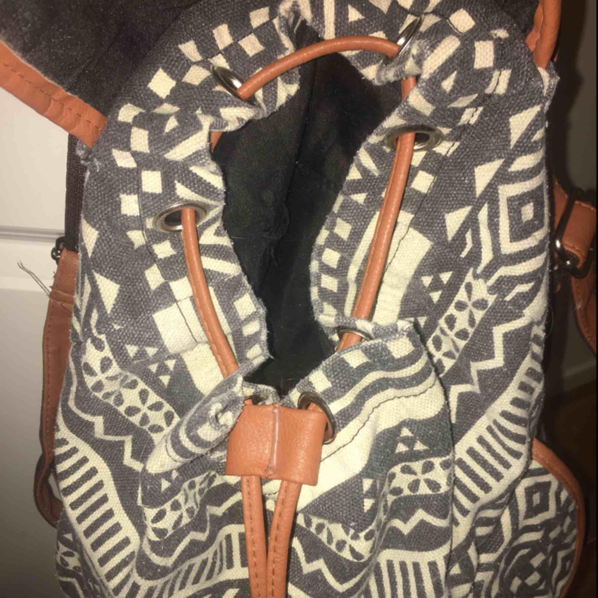 Svart och vit-mönstrad ryggsäck från okänt märke. Väskans band och detaljer är av metall och fakeläder! Det finns många fack så den är väldigt praktisk! Väskan är använd så lite sliten men inget som märks! Köpare står för frakt!🌙🧚♀️  . Väskor.