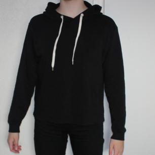 Svart hoodie med vita snören - 60 % bomull, 40% polyester - Frakt ingår i priset