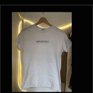 """Vit t-shirt från Decksclothing med texten """"sunflower wolf"""" broderat över bröstet. Strl. S, Pris: 55kr. BETALNING SKER VIA SWISH:FRAKT INGÅR I PRISET"""