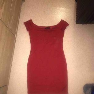 En röd fin off shoulder klänning som når lite över knäna