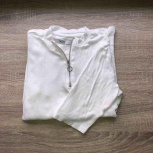 Vit topp med dragkedja. Lite längre ärmar än en vanlig t-shirt. Storlek S