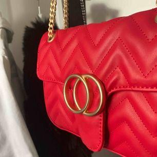 Röd väska som kan användas både som crossover men även som en axelväska som bild 1! Aldrig använd, säljer pga av jag inte gillar gulddetaljer längre tyvärr 😭