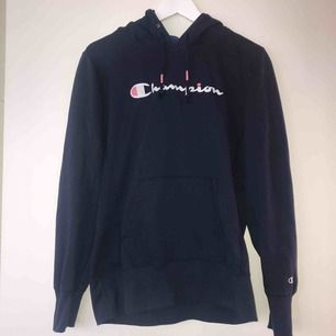 Marinblå hoodie från Champion i tunnare material med broderade detaljer (på luvan och frampå) i vitt och rosa. Liten i storleken! Köpt från Junkyard för ett år sedan för cirka 700 kr och är max använd 3 gånger. Säljs för 350 kr och i priset ingår frakt.