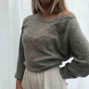 Grå stickad tröja med större urringning, kan användas som off shoulder. Köparen står för frakten.