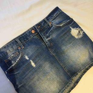 En blå sliten jeanskjol från ginatricot