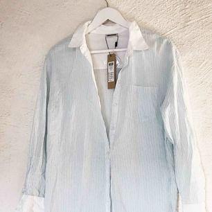 Fin ljusblå- och vitrandig skjorta från Noisy May. Aldrig använd; prislappen hänger kvar med extra knappar (nypris 299 kr). Ursäkta att den är skrynklig, legat i garderoben. 🥰 Frakt tillkommer 🌹