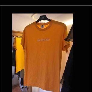 Gul/orange-ish t-shirt från Decks Clothing i S. Broderad text: SUNFLOWER WOLF, över bröstet. Pris: 65kr. BETALNING SKER GENOM SWISH:FRAKT INGÅR I PRISET