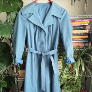 Ljusblå/duvblå vintage trenchcoat i storlek ca 36-38. Väldigt fint skick.
