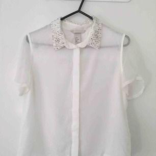 Genomskinlig kortärmad vit blusa med vit/silver pärlor på kragen. Stl 36. H&M