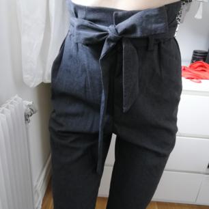 Helt nya och oanvända gråa paperbag byxor med knyt i midjan. Från hm