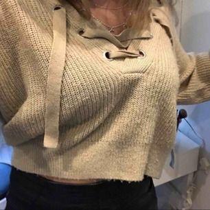 Fin beige stickad tröja med snörning fram, väldigt fin att antingen ha offshoulder eller över ena axeln! Fraktkostnad tillkommer