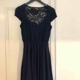 Mörkblå klänning med spets. Använd endast en gång på ett bröllop.