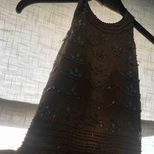 En mörkbeige långklänning med fina detaljer från Nelly! Använd en gång, så i mycket bra skick!