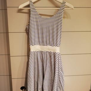 Blå/vit randig klänning med markerande midja. Djup i ryggen, använd sparsamt.