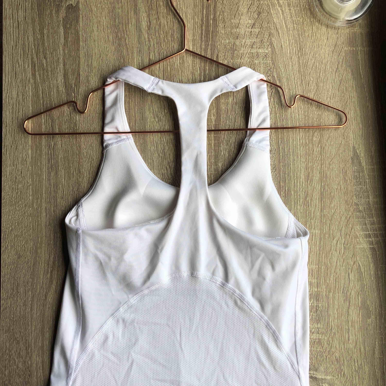 Vit stretchig träningsstopp från Nike. Material: Dri-Fit. Använd endast en gång. Ber om ursäkt för de skrynkliga 🙈. Toppar.