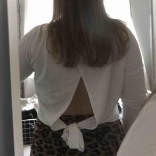 Vit tröja med öppen rugg med knyte längs ner. Köparen står för frakten