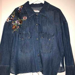 Supersnygg jeansskjorta med brodyr på ena axeln samt slitage längst nederkant. Använd en gång. Så som ny. Storlek S, passar fint för en XS/M likaså.  Nypris 600&.