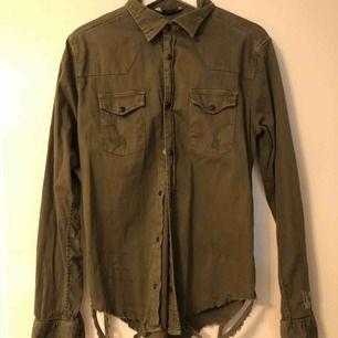 Militär grön skjorta med sliten nederkant.  Storlek M men skulle säga att den är mellan s/m. Aldrig använd. Nypris 400kr.