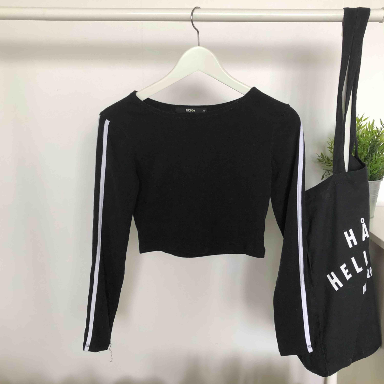 Svart långärmad tröja ifrån Bik Bok med två vita ränder på ärmarna! Jätteskönt material, croppad 💕 Gratis frakt. Toppar.