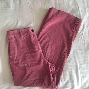 Rosa manchesterbyxor med vida ben. Fickor fram, bakfickor med knapp. Endast använt ett fåtal gånger. Köpta detta år.